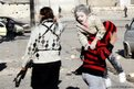 A man carries a wounded girl way from the scene of what activists describe as an air strike in Aleppo by forces loyal to Syrian President Bashar al-Assad.