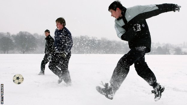 Youngsters play football in the snow