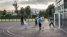 Children play football in the shadow of the London 2012 Olympic Park