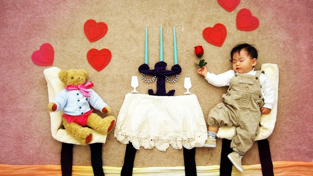 Photograph of staged scene of sleeping baby dining with a bear