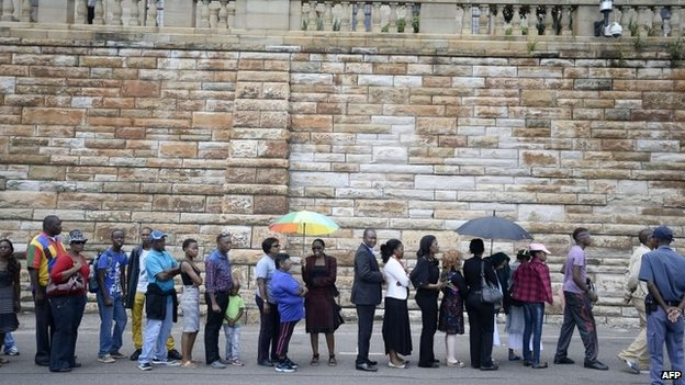 South Africans stand in line to pay their respect to South African former president Nelson Mandela