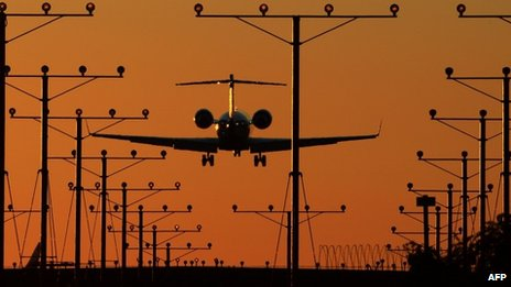 A plane comes in for a landing at Los Angeles International Airport (LAX) at dusk 1 November 2013
