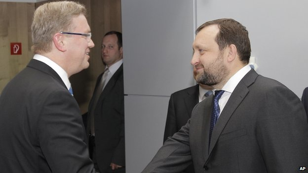 European Commissioner for Enlargement and European Neighborhood Policy Stefan Fuele, left, shakes hands with Serhiy Arbuzov, Ukrainian Deputy Prime Minister, at the European Commission headquarters in Brussels, Thursday, Dec. 12, 2013