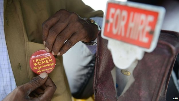 """An Indian auto driver pins on an """"I respect women"""" badge from the Andhra Pradesh Tourism Department during World Tourism Day celebrations in Hyderabad"""
