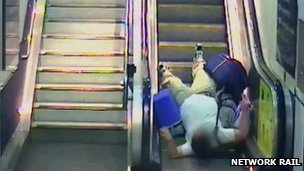 Man falling on escalator