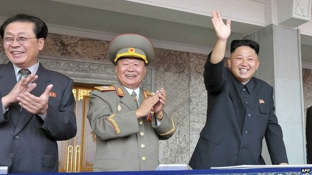 This file picture taken by North Korea's official Korean Central News Agency (KCNA) on 9 September 2013 shows North Korean leader Kim Jong-un (R), accompanied by his uncle Chang Song-Thaek (L), waving as he inspects a mass parade of the Worker-Peasant Red Guards at Kim Il-Sung Square in Pyongyang to mark the 65th anniversary of the national foundation day