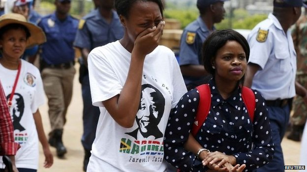 A woman reacts after paying her respects to former South African President Nelson Mandela on the last day of Nelson Mandela's lying in state at the Union Buildings in Pretoria, 13 December 2013