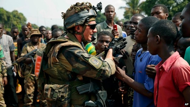 French troops try to calm the crowds before pulling out and letting Fomac troops, regional force, evacuate Muslim clerics from the St Jacques Church in Bangui, Central African Republic, Thursday 12 December 2013