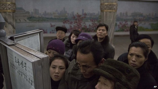 North Korean subway commuters gather around a public newspaper stand on the train platform in Pyongyang, North Korea on Friday, Dec. 13, 2013 to read the headlines about Jang Song Thaek