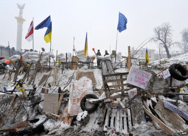 Protesters guard a barricade in Kiev, 13 December