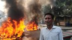 A Bangladeshi man stands near his burning vehicle, set on fire by demonstrators following the execution of a senior Jamaat-e-Islami leader, Abdul Kader Mullah, in Dhaka on 13 December