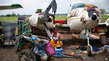 A woman and baby shelter near a plane at Bangui airport, CAR (13 Dec 2013)