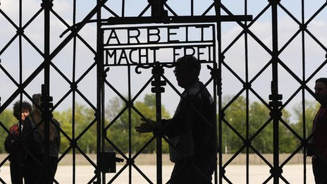 Visitors walk past a gate with 'Work makes you Free' written on it at the memorial site of the former Nazi concentration camp in Dachau, file image