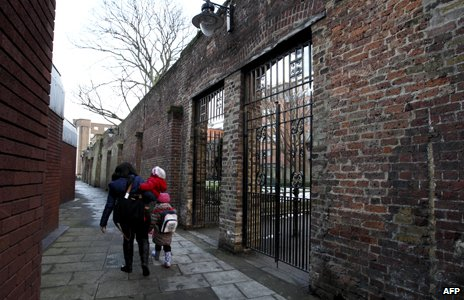 Woman and child walk past remaining wall of Marshalsea prison in London, 2012