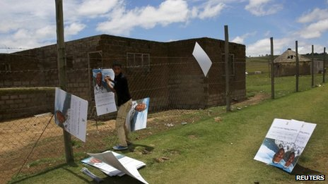 A man places a poster of Nelson Mandela on a fence at the perimeter of the former president's property in Qunu, on a blustery day.