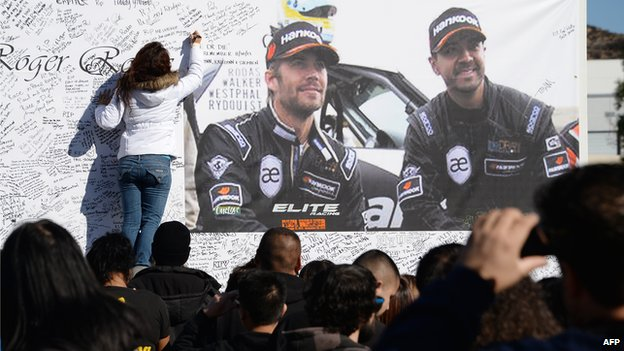 A woman signs a memorial to Paul Walker and friend Richard Rodas