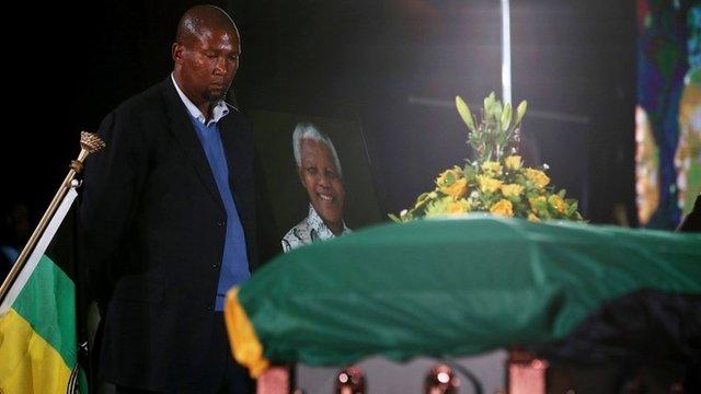 Mandla Mandela, stands next to his grandfather's coffin