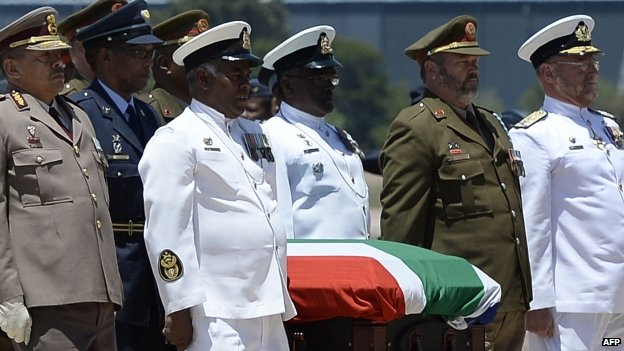 Officers carry Nelson Mandela's coffin on to a C130 military transport plane