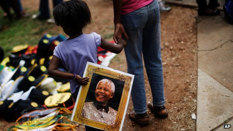 Girl with picture of Nelson Mandela in Pretoria on 11 December