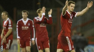 Aberdeen players celebrate at the full-time whistle in front of a crowd of over 9,000