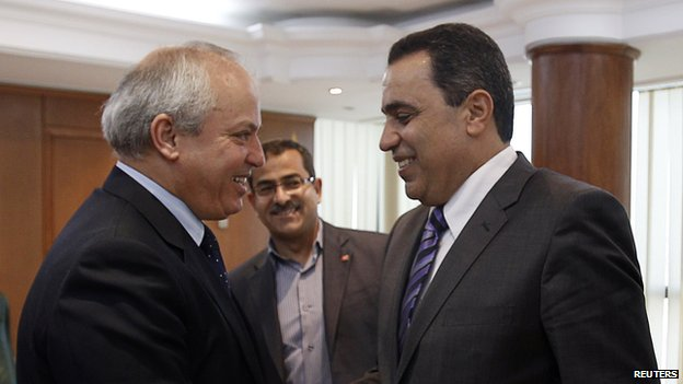 Mehdi Jomaa (R) shakes hands with Libyan Oil Minister Abdelbari al-Arusi in Tunis April 12, 2013