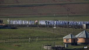 Members of the South African navy are lining the road from the Mandela family house to his burial site