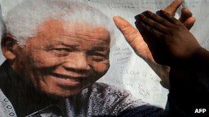A woman touches the hand on a Nelson Mandela portrait in Pretoria