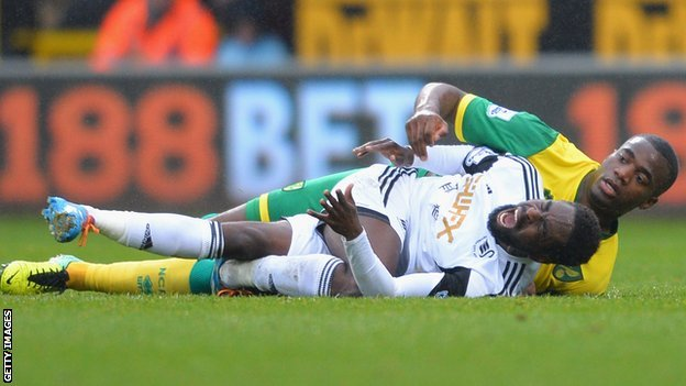 Swansea City's Nathan Dyer in pain after he fell heavily under Norwich City's Sebastien Bassong.