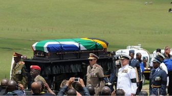 Nelson Mandela's coffin is taken to his final resting place in Qunu by a military guard of honour