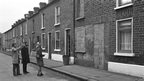 Three people examine terraced houses