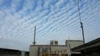 Patterned clouds in a blue sky. Below is a tarmac works.