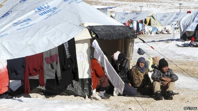 Syrian refugees sit by their tent in a Syrian Refugee camp on the Lebanese border town of Arsal