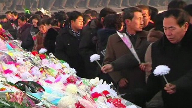 North Koreans lay flowers