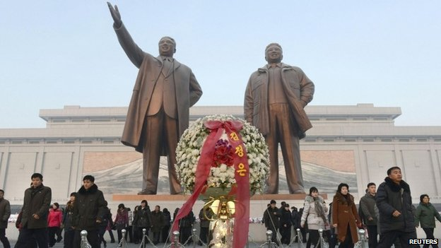 North Koreans walk near the statues of Kim Il-sung and Kim Jong-il