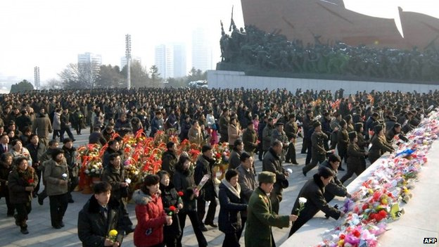 This picture taken by North Korea's KCNA on 16 December 2013 shows people offering flower bouquets before the statues of late North Korean leaders Kim Il-sung and Kim Jong-il to mark the second anniversary of Kim Jong-il's death