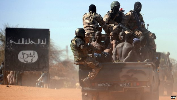 Malian soldiers transport in a pickup truck a dozen suspected Islamist rebels in February 2013
