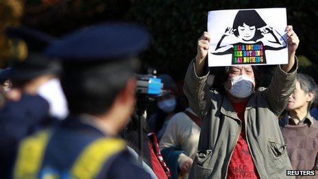 People protest against the proposed state secrets act in front of the parliament building as a policeman looks at in Tokyo