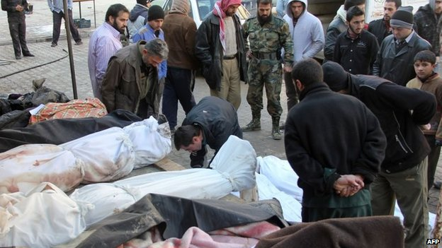 People inspect the bodies of people killed in air strikes in Aleppo's Maadi district (17 December 2013)