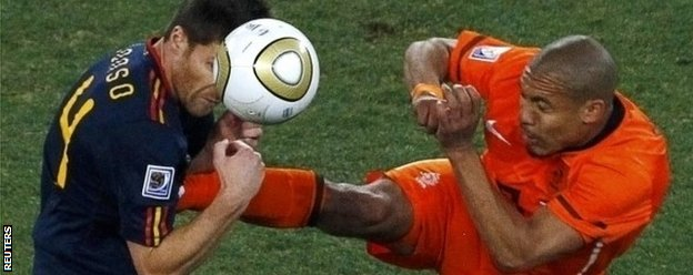 Nigel de Jong tackles Xabi Alonso