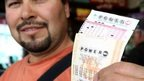 A man holds a Powerball lottery ticket.