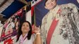 Khamsaen Chaithep, wife of the village chief in Nhong Huu Ling, stands by a poster of Thaksin Shinawatra