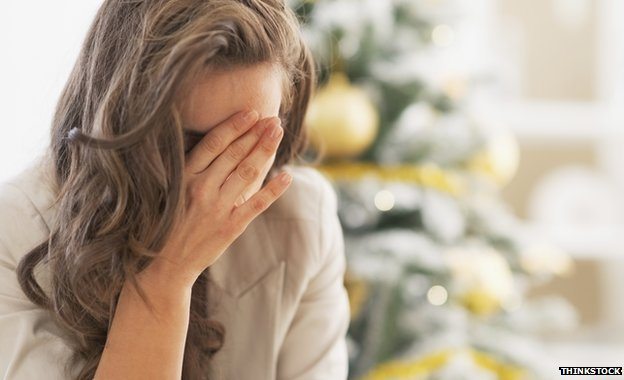 Woman looking stressed in front of Christmas tree