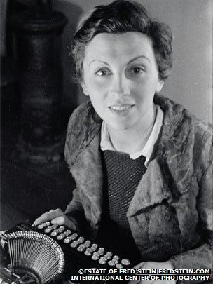 Gerda Taro sitting at a typewriter