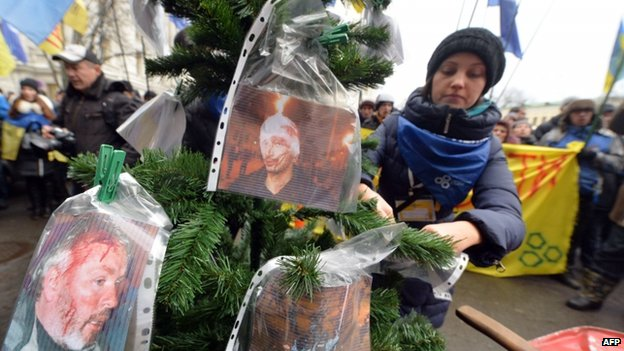 An opposition activists hangs pictures of injured protesters during clashes with riot police to a Christmas tree during an action in front of Rinat Akhmetov office in Kiev on December 18, 2013