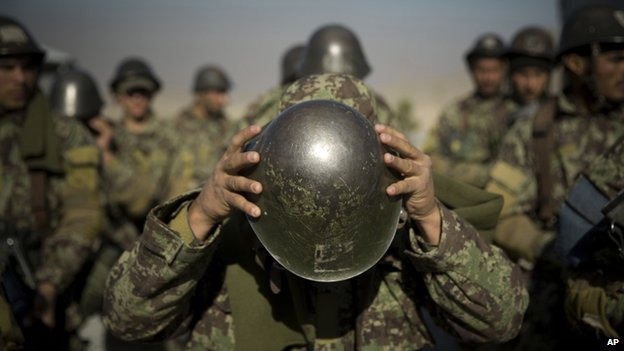 An Afghan army soldier adjusts his helmet as he lines up with others at a training facility in the outskirts of Kabul, Afghanistan