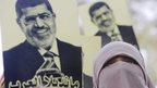 "A supporter of Mohammed Morsi in Cairo holds up a picture of him that says: ""Mandela of the Arabs"" (22 November 2013)"
