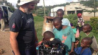 Cameraman with locals in Rwanda