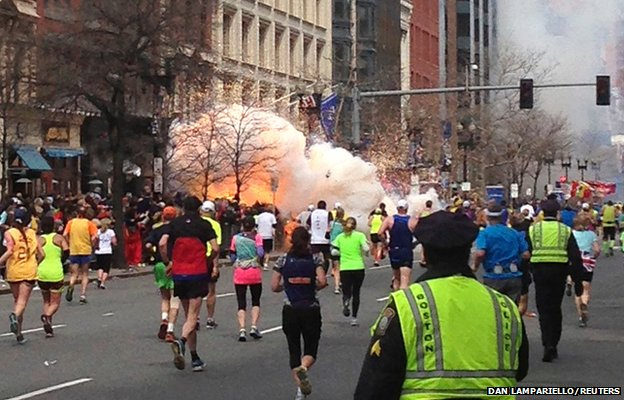 Runners continue to run during the Boston Marathon as an explosion erupts near the finish line