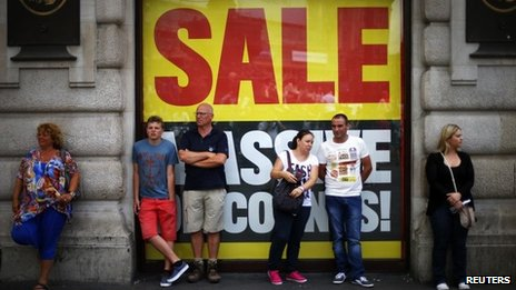 Sale sign and shoppers