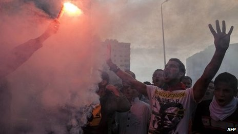Muslim Brotherhood and ousted President Mohamed Morsi supporters light up a flare and shout slogans during during a demonstration in Cairo